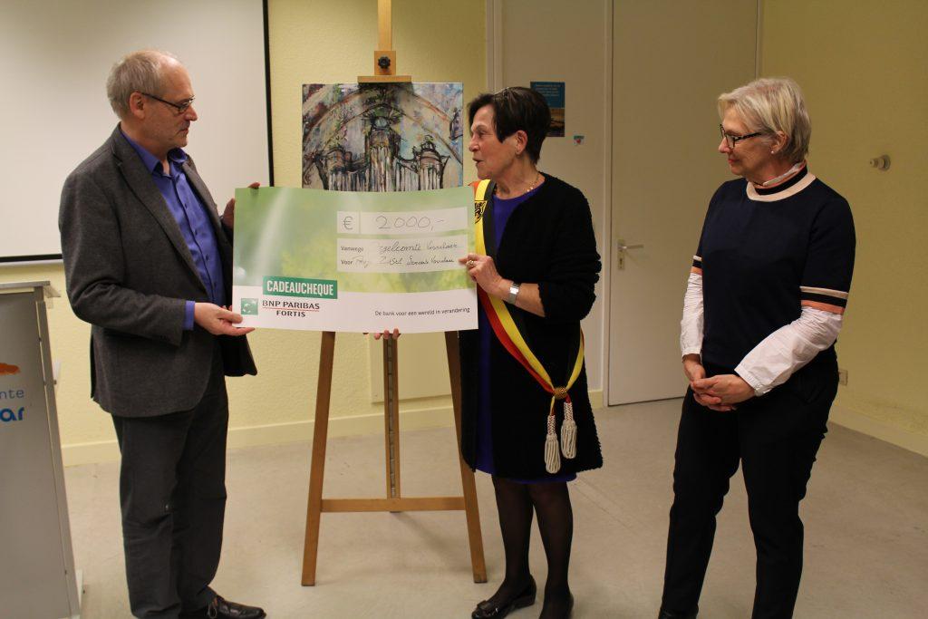 Jan Robrechts overhandigt de cheque van 2000 euro aan burgemeester Josee Heykants-Jansen.